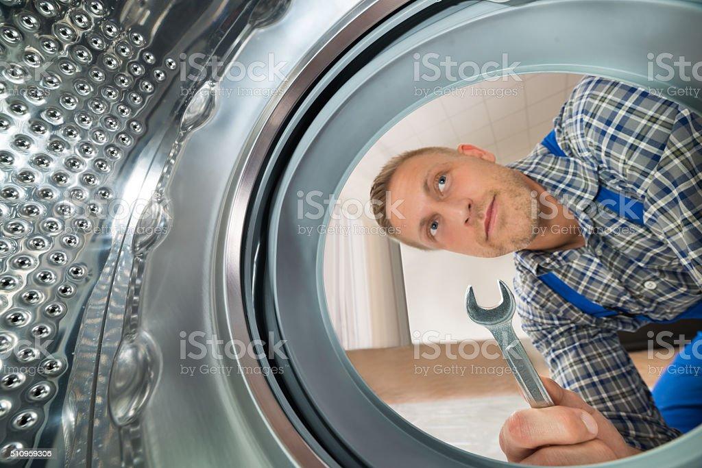 Reparador mirando dentro de la máquina de lavado foto de stock libre de derechos