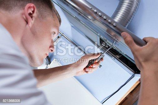istock Repairman mending a kitchen extractor 521368005