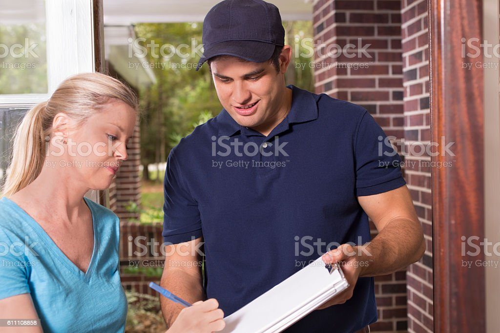 Repairman or delivery person at customer's front door. Latin descent blue collar/service industry worker or delivery person makes service/house call at customer's front door.  He holds a clipboard while customer signs.  The man wears a blue uniform.  Inspector, exterminator, electrician, plumber, delivery driver.  Red brick home. 20-29 Years Stock Photo