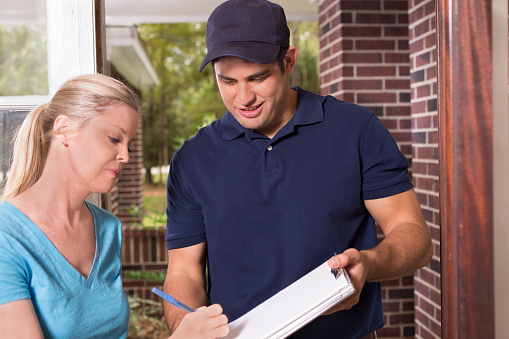 Repairman Or Delivery Person At Customers Front Door Stock Photo - Download Image Now