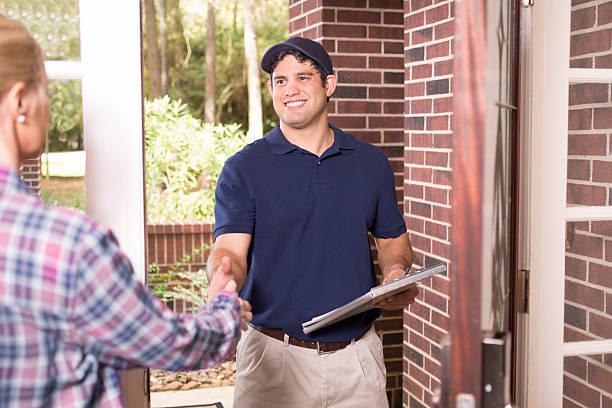 repairman or delivery person at customer's front door. - consertador - fotografias e filmes do acervo