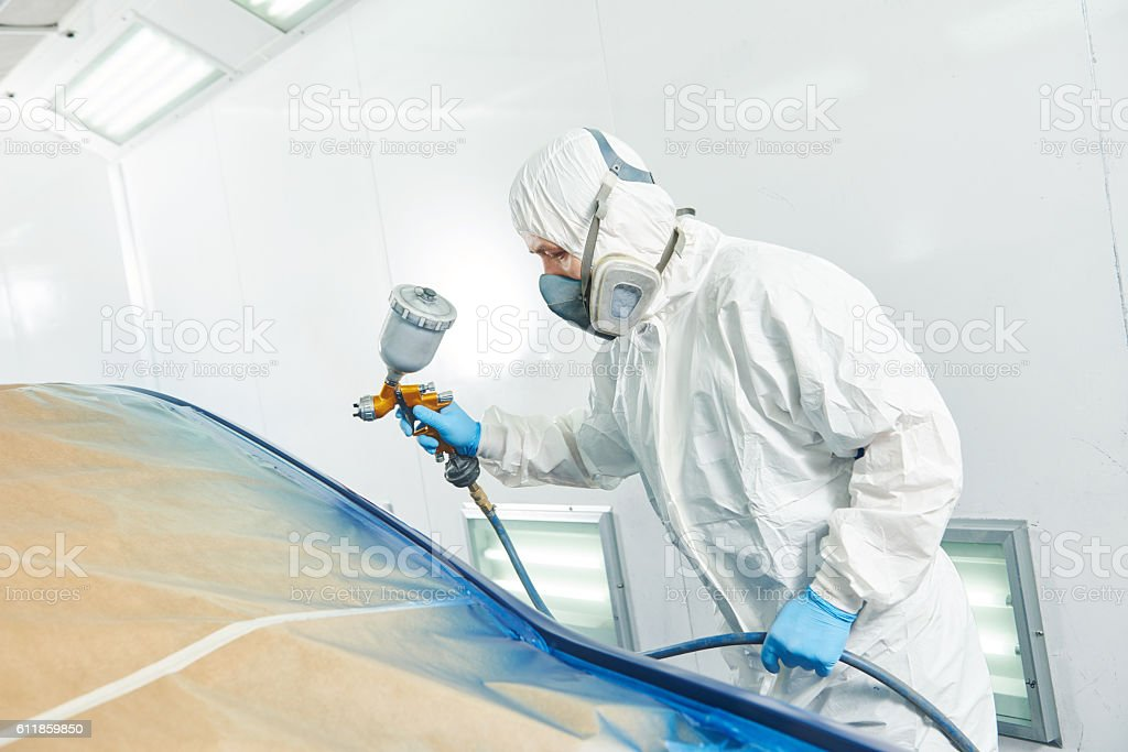 repairman painter in chamber painting automobile car bumper stock photo