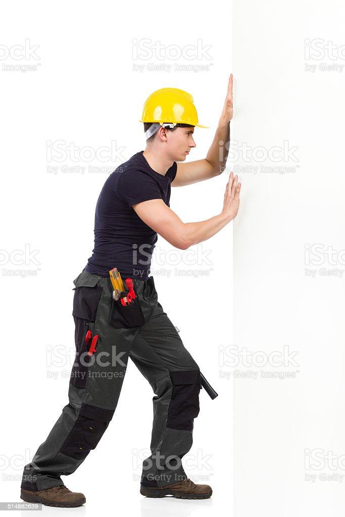 Repairman pushing the wall stock photo