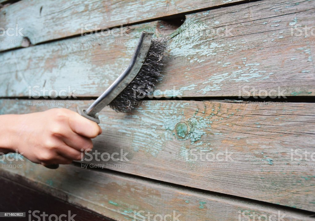 Repairman remove the old paint from the wooden surface with  wire brush. stock photo