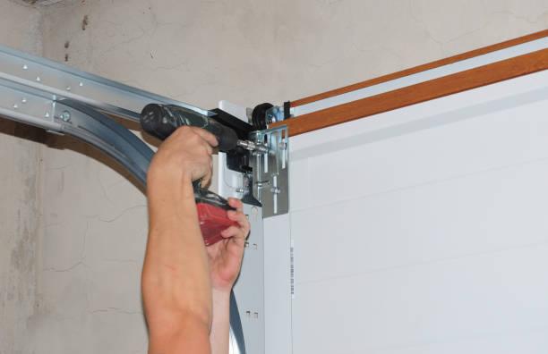 Reparateur reparatie garagedeur opener. Garagedeur vervanging, garagedeur reparatie. foto