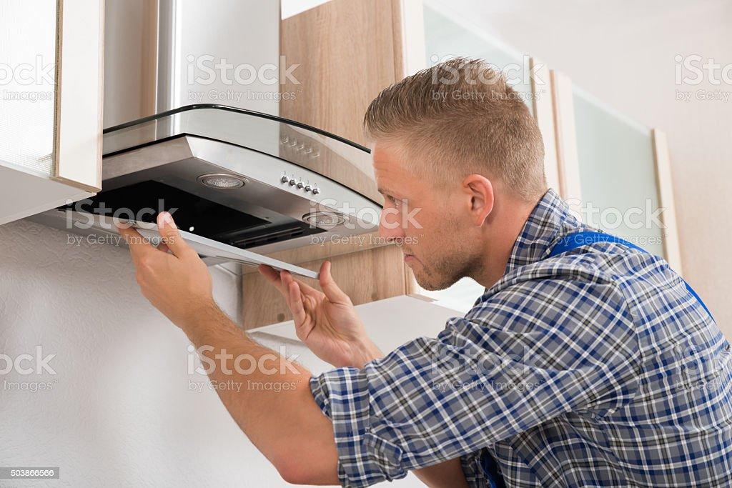 Handwerker reparatur küche extraktor filtern stock fotografie und