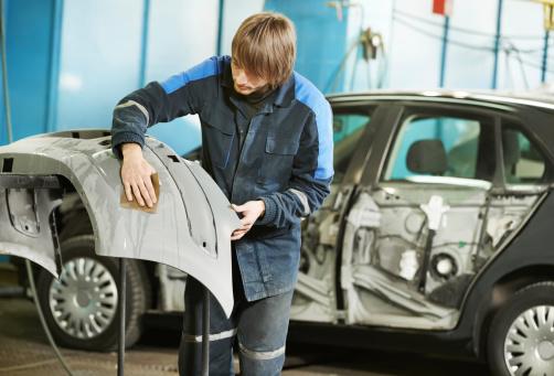 istock repairman sanding plastic car bumper 166438396