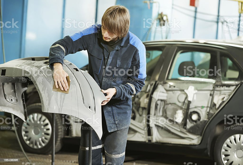 repairman sanding plastic car bumper stock photo