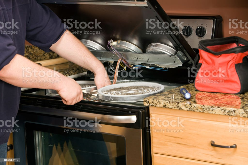 Repairman Servicing an Electric Kitchen Range stock photo