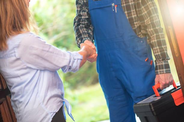 Repairman shaking hands with customer, light effect stock photo