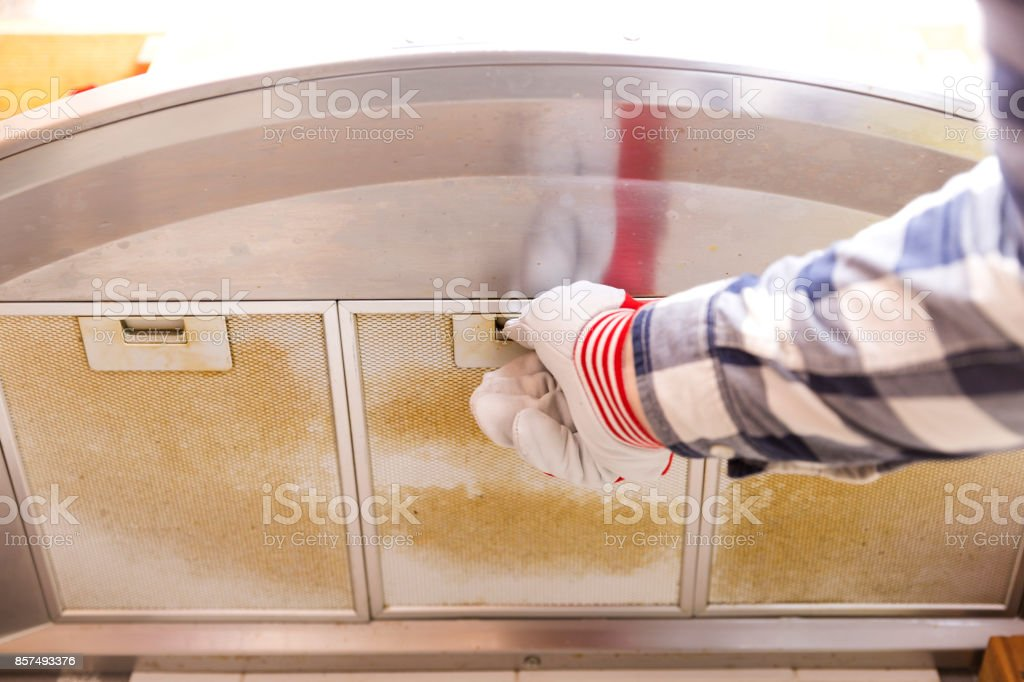 Repairman taking filthy aluminum mesh filter out of the cooker hood stock photo