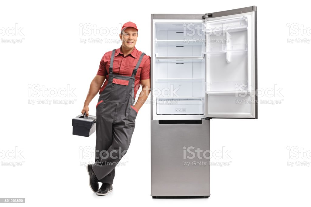 Repairman with a toolbox leaning against an open fridge royalty-free stock photo