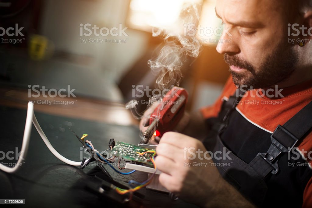 Repairman working in workshop and soldering electric board stock photo