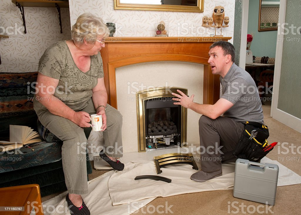 Repairman Working on Fireplace for a Senior Woman royalty-free stock photo