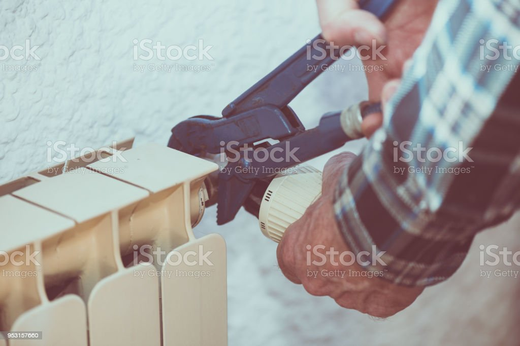 Repairman working on radiator with wrench stock photo