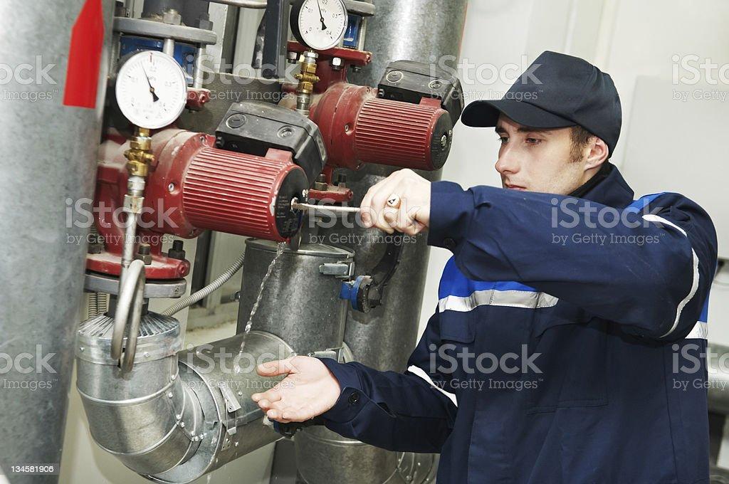 Repairman working on water pump in boiler room stock photo