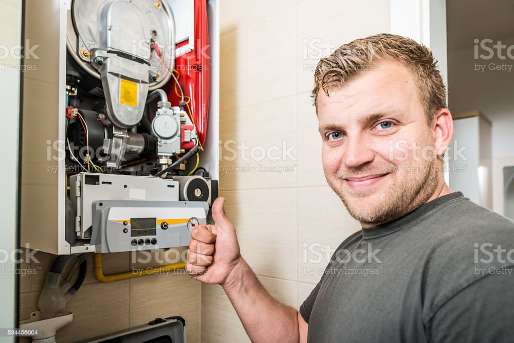 Repairman works on furnace stock photo