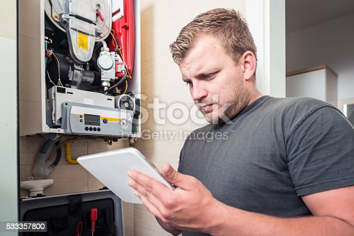 istock Repairman works on furnace using tablet 533357800