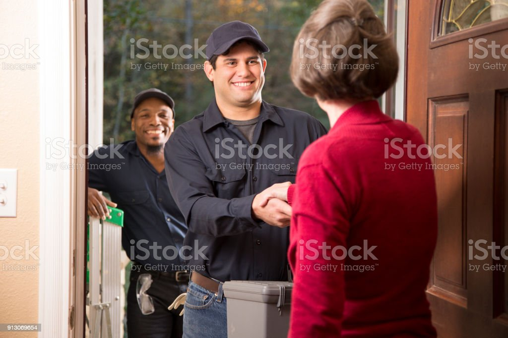 Repairmen arrive at customer's front door for home repairs. stock photo