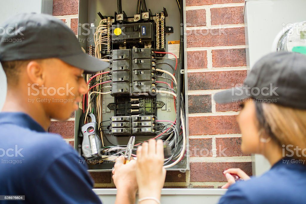 Repairmen, electricians repairing home breaker box. stock photo