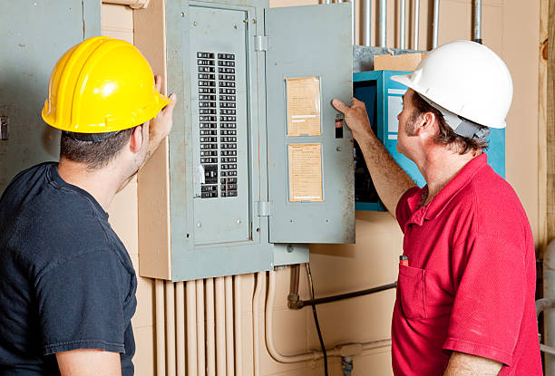 repairmen examine electrical panel - fuse box stock photos and pictures