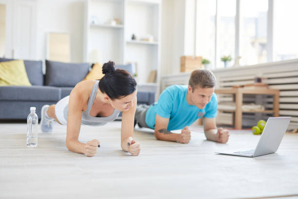 Repeating after online trainer Contemporary young active couple in sportswear doing planks on the floor in front of laptop while watching online workout exercising stock pictures, royalty-free photos & images