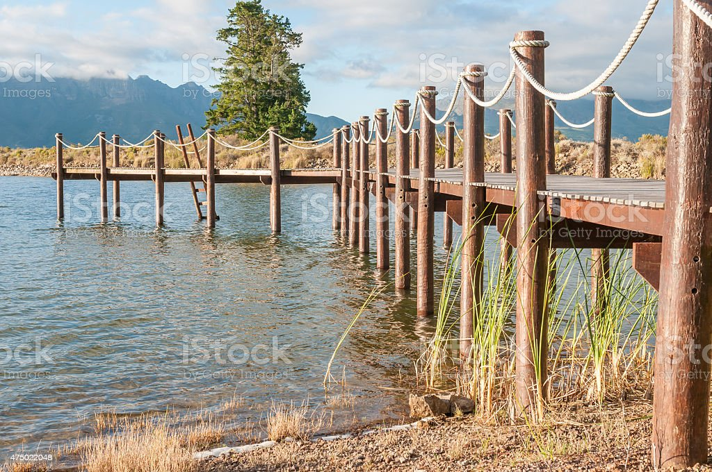 Repeating pattern of wooden poles in a jetty stock photo