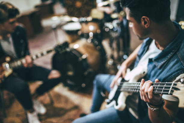 Repetition of rock music band. Repetition of rock music band. Bass guitar player, electro guitar player and drummer behind the drum set. Rehearsal base practicing stock pictures, royalty-free photos & images