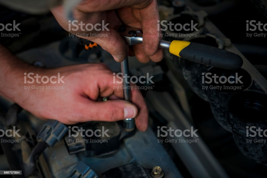 Replacement of spark plugs in the car. Hands of the master. stock photo