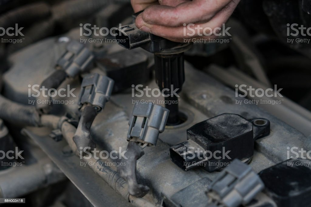 Replacement of spark plugs in the car. Repair of the old machine. Hands of the old elderly master. stock photo