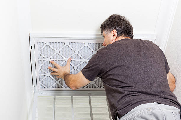Replacing AC Filter Man replacing a filter on a home air conditioning system. lighting technique stock pictures, royalty-free photos & images