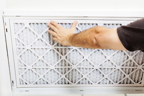 Man replacing A/C filter for a home air conditioning system.
