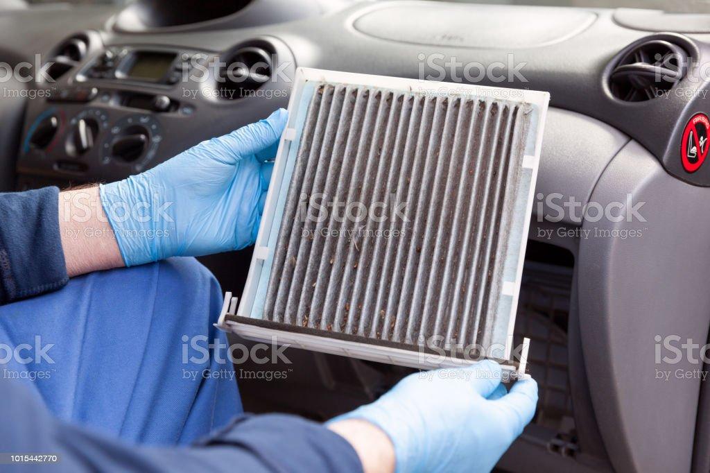 Replacing an old car cabin air filter stock photo