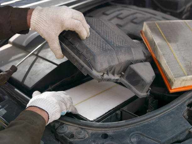 replacing car air filter Hands of mechanic replacing car air filter, outdoor closeup air filter stock pictures, royalty-free photos & images