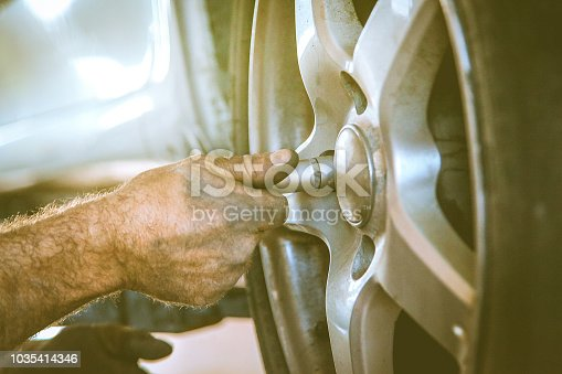 498888104 istock photo Replacing car wheel and tyre 1035414346