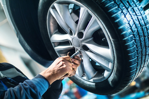 Closeup of unrecognizable male mechanic unscrewing the bolts on the rim of car wheel in order to replace tyre or the wheel itself. After he got those bolt loose with power tool he's using hand screwdriver to pull them out. The mechanic is wearing blue working uniform and the wheel is lit with blue fill light. The car is lifted up on a car jack