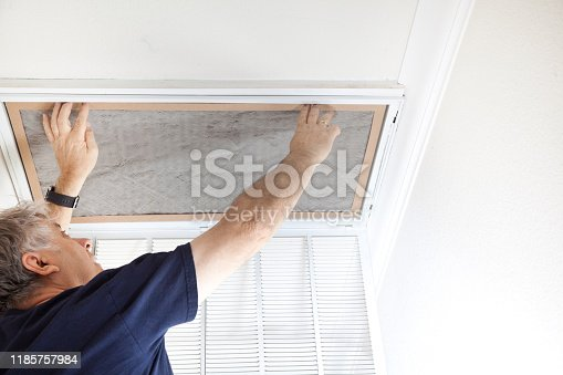 Man replacing dirty air conditioning filter at home.