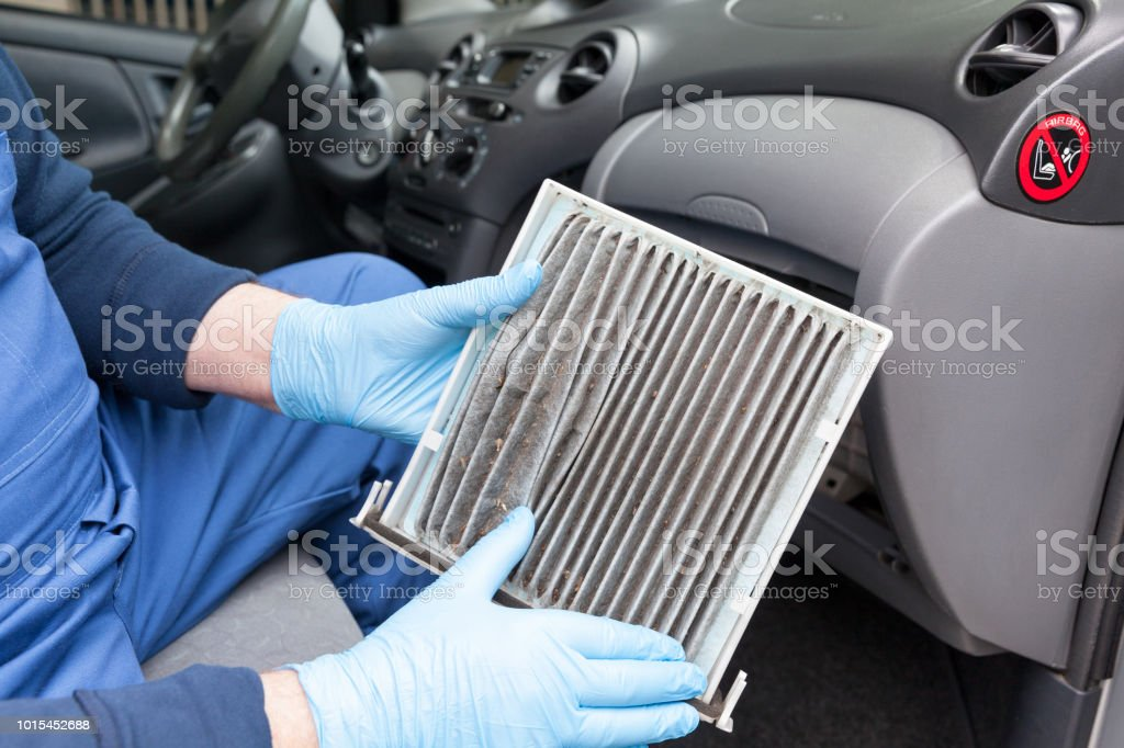 Replacing dirty cabin pollen air filter for a car stock photo