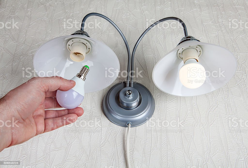 Replacing electric lightbulbs in household wall lamp, LED light stock photo