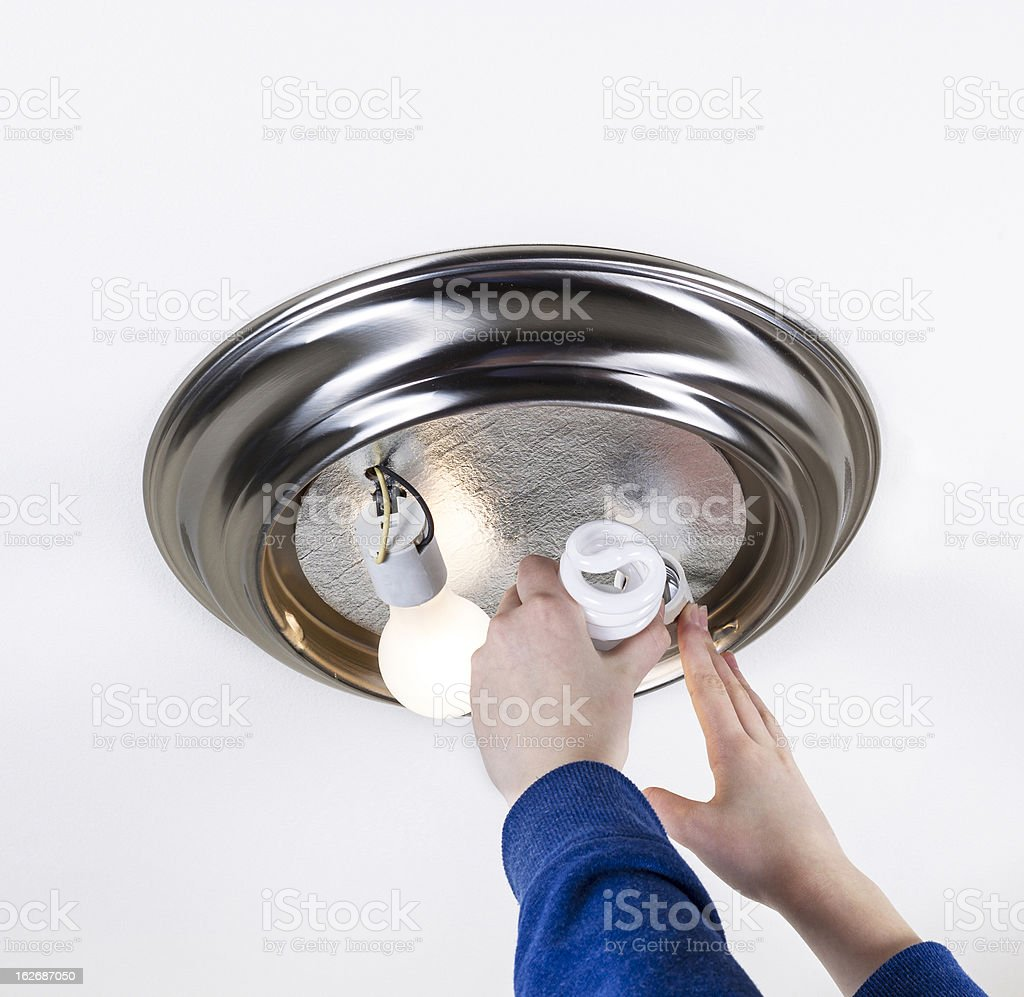 Replacing Light Bulb with Compact Fluorescent One royalty-free stock photo