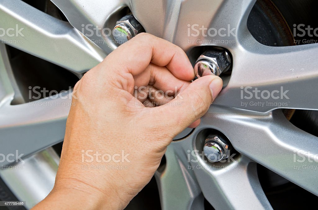 Replacing lug nuts by hand. stock photo