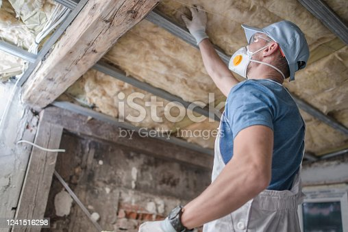 Caucasian Contractor Worker in His 30s Replacing Old Attic Mineral Wool Insulation. Wearing Safe Breath Pro Mask. Industrial Home Improvement and Insulation Materials Theme.