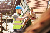 a builder or roofer is removing a finial on a roof of a period property in england .