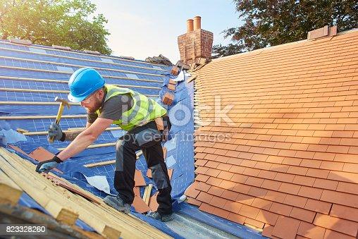 istock replacing roof tiles 823328260