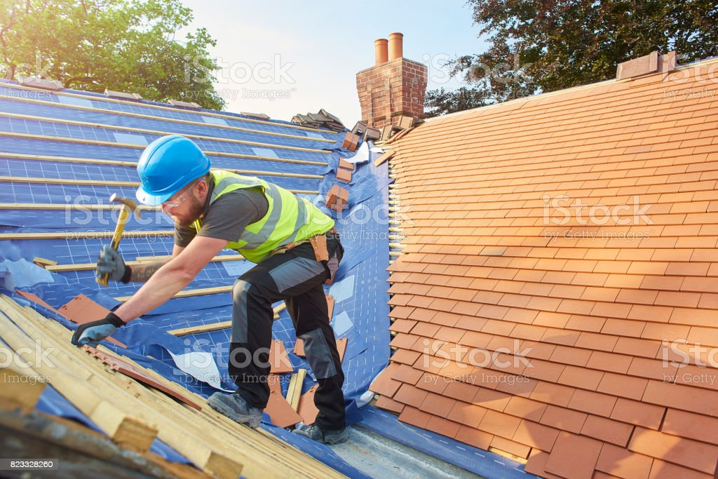 replacing roof tiles stock photo