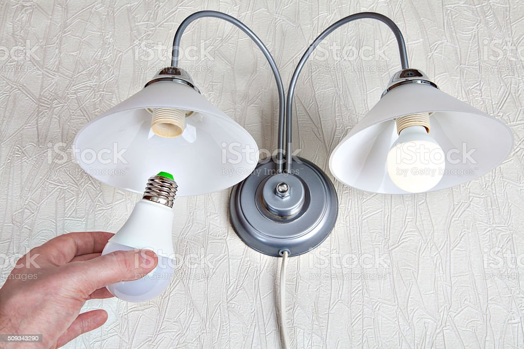 Replacing the bulbs in wall lights, hand holds  LED lamp. stock photo