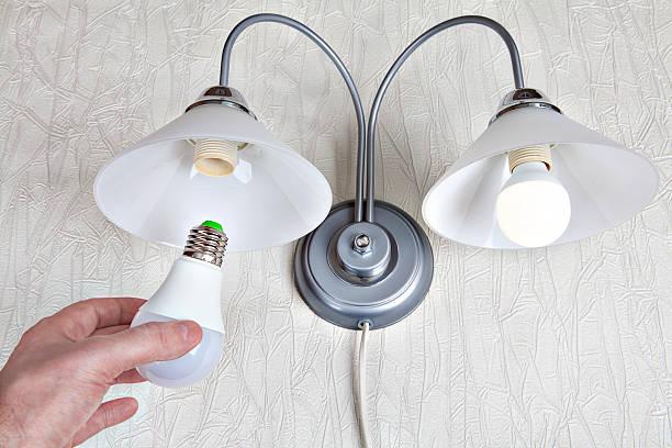 ersetzt die glühbirnen in wandleuchten, hand-halterungen led-lampe. - glühbirne auswechseln stock-fotos und bilder