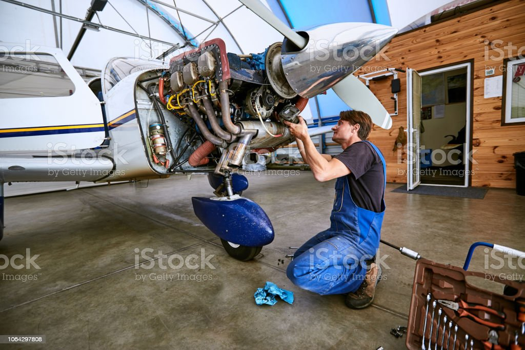 Replacing the defective parts of the aircraft service worker. stock photo