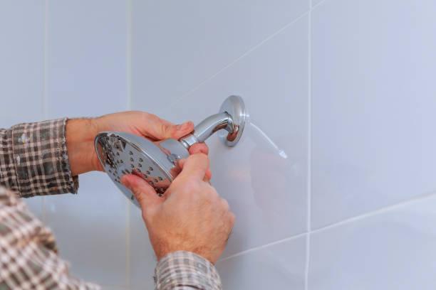 substituindo o encanamento no banheiro montou o suporte do chuveiro da mão com altura ajustável uma cabeça de chuveiro. - banheiro instalação doméstica - fotografias e filmes do acervo