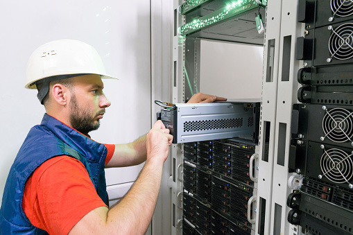 . Replacing the power module in the server room rack. Maintenance of data center equipment. The technician installs a new battery pack into the uninterruptible power supply